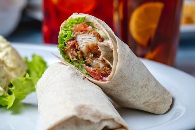 Вид сбоку куриный рулет жареные куриные полоски с помидором майонез и салатом, завернутым в тортилью