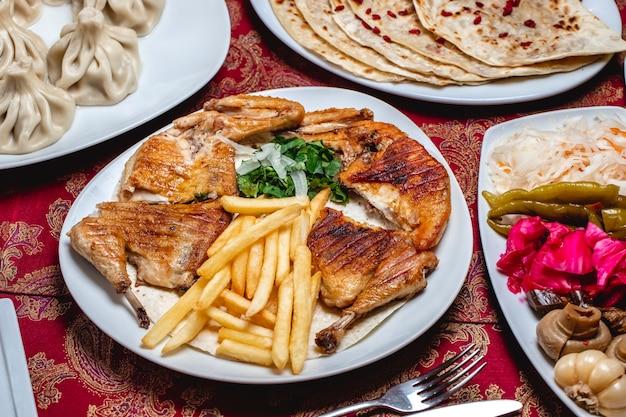 サイドビューチキンタバカとフライドポテトのグリーン玉ねぎのピクルスキノコキャベツコショウナスとニンニクのテーブル