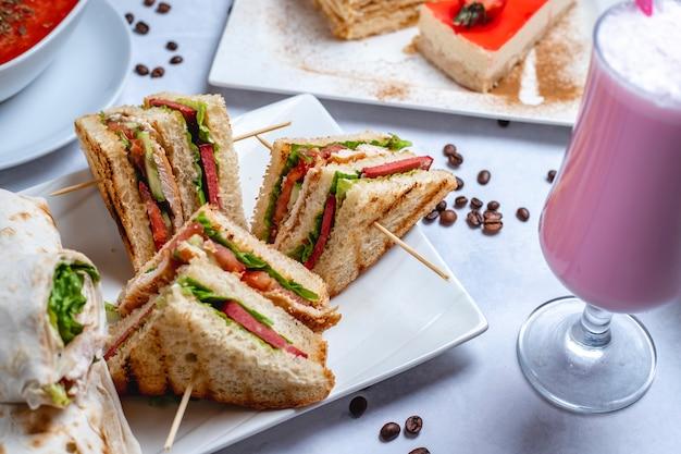 Боковой вид клубный сэндвич на гриле курица с огурцом томатный соус, салат, молочный коктейль и кофейные зерна на столе