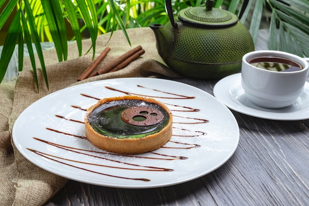 Вид сбоку печенье с желе и шоколадной глазурью с чашкой чая