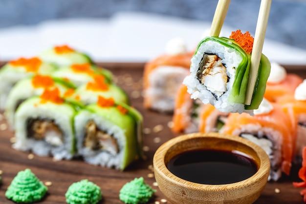 Вид сбоку ролл дракона с огурцом, жареной рыбой, икрой тобико, кунжутом, соевым соусом и васаби на доске