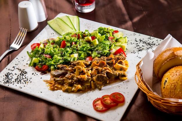 Вид сбоку жареного мяса с грибами в соусе с овощным салатом и ломтиками помидора и огурца