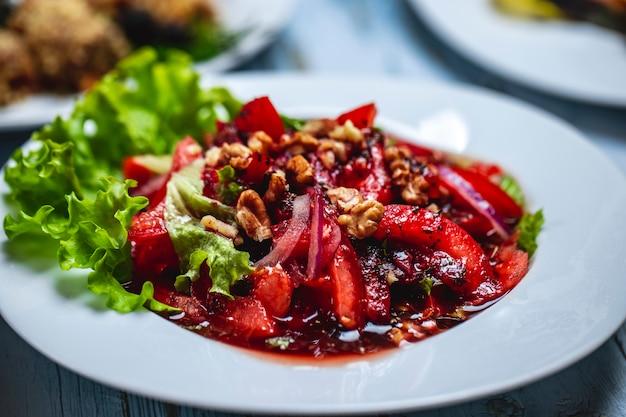 Вид сбоку грузинский салат с нарезанными помидорами соусом из красного лука и грецкого ореха со сливой и салатом на тарелке