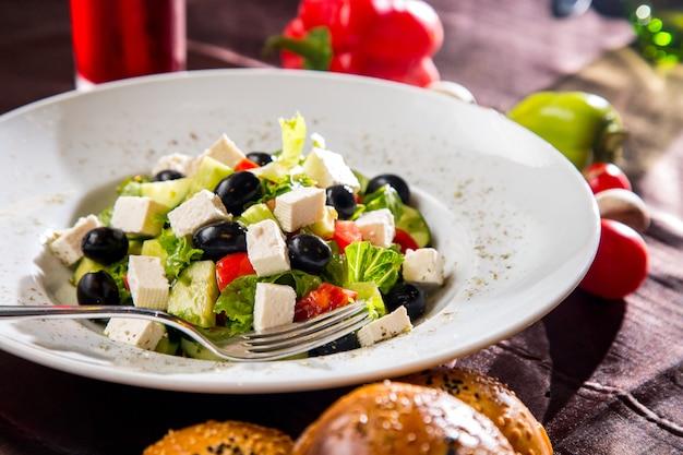 サイドビューのギリシャ風サラダ、ブラックオリーブのパンとキノコ