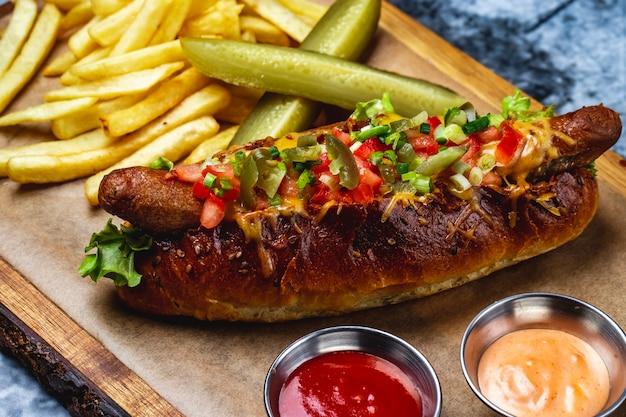 Вид сбоку хот-дог на гриле, колбаса с томатной зеленью, плавленый сыр, перец халапеньо в хот-дог, булочка с картофелем фри, соусы и маринованный огурец на доске