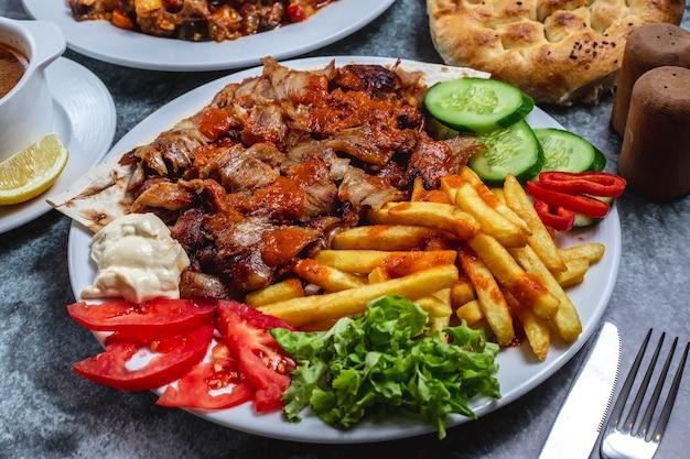 Вид сбоку донер на тарелку с картофелем фри помидор свежий огуречный йогурт и хлеб на столе
