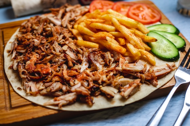Вид сбоку донер на лаваш с картофелем фри свежий огурец и помидор