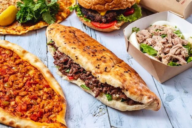 Вид сбоку мясной донер с хлебом на гриле, салатом и помидорами на столе