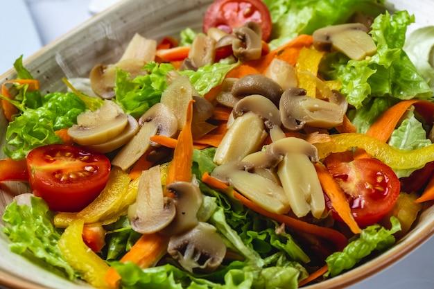 側面図きのこのサラダキノコのピクルスオレンジピーマンキャロットレタスとトマトの皿の上