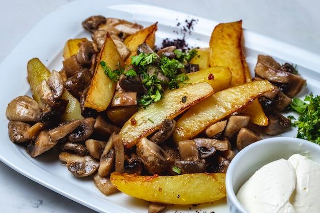 キノコのフライドポテトとシャンピニオングリーンとテーブルの上のサワークリームとサイドビューポテト