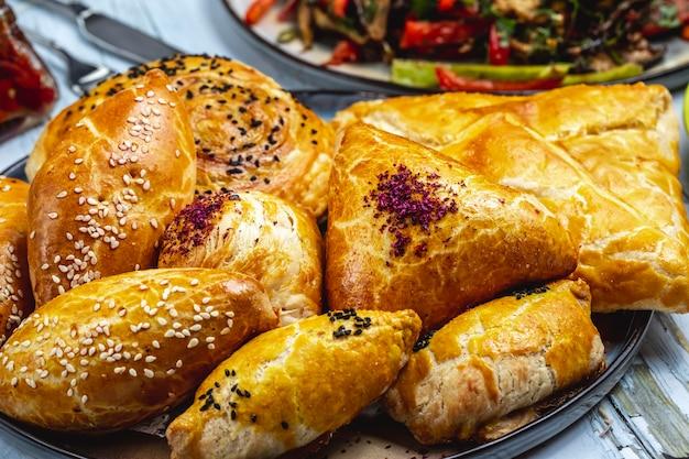 Вид сбоку слоеного теста с мясом кунжута и песочное печенье с картофельным пюре на столе