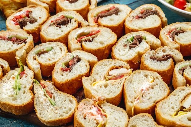 Вид сбоку бутерброды из белого хлеба с жареной курицей, говядиной, огурцом, помидором, салатом и сыром