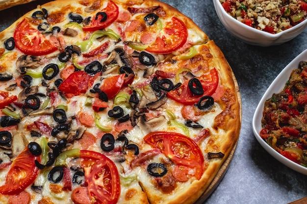 テーブルの上のトマトピーマンスモークソーセージブラックオリーブとチーズのソーセージピザの側面図