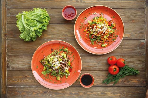 Вид сверху двух красных тарелок овощных салатов