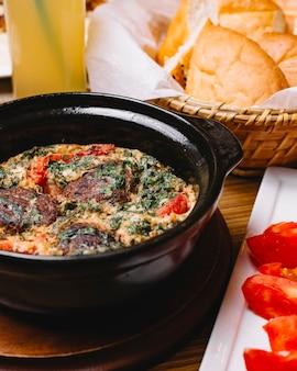 Вид сбоку яичница-болтунья с фрикадельками и зеленью в нарезанной сковороде ‹помидор и хлеб