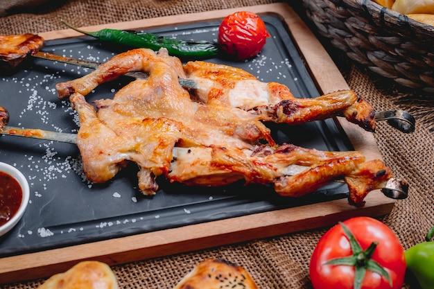Боковой вид табака на шампурах с солью и овощами гриль