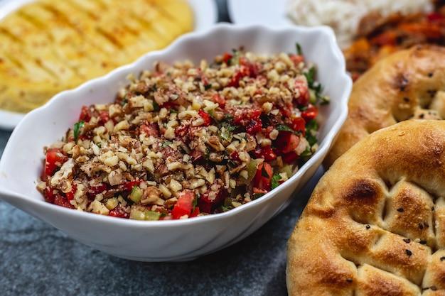 Вид сбоку салат из грецких орехов с томатной огуречной зеленью и хлебом на столе