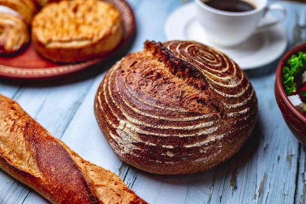 テーブルの上のバゲットパンと一杯のコーヒーと酵母無料パン