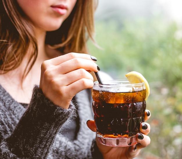 女性がレモンのスライスでさわやかなカクテルを飲む側面図