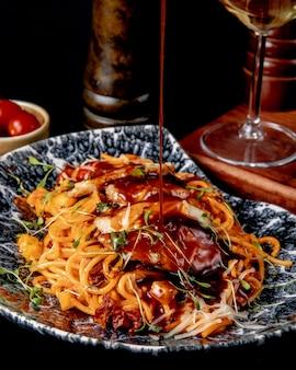 Томатный соус наливают спагетти с курицей, вид сбоку