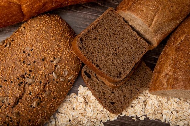 木製の背景にオート麦フレークとサンドイッチパンライ麦パンバゲットパンとしてパンのクローズアップビュー