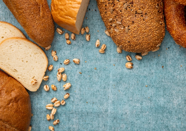 コピースペースと青の背景に白パンのスライスと他の種類のパンとトウモロコシのクローズアップビュー