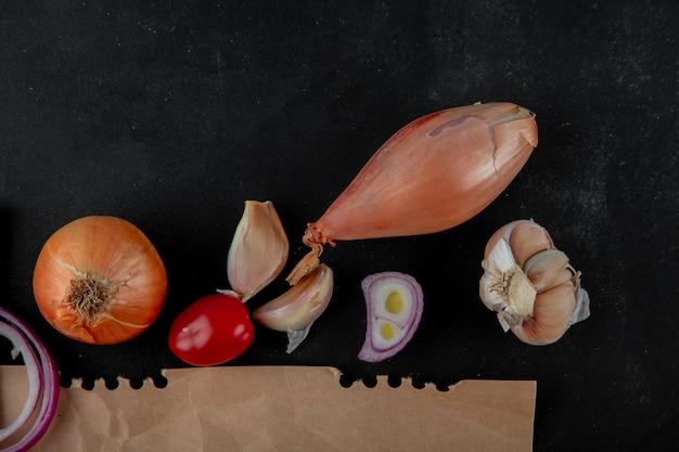 Взгляд конца-вверх овощей как чеснок шалота томата лука на черной предпосылке с космосом экземпляра