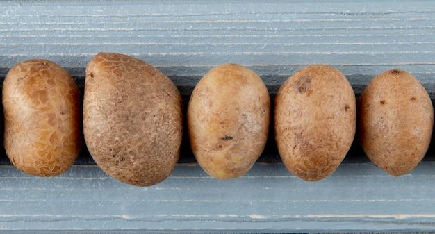 コピースペースを持つ木製の背景にジャガイモのクローズアップ表示
