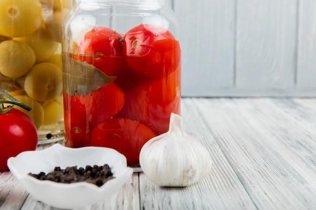 木製の表面とコピースペースと背景にニンニクと黒コショウのピクルストマトがいっぱい入った瓶のクローズアップ表示
