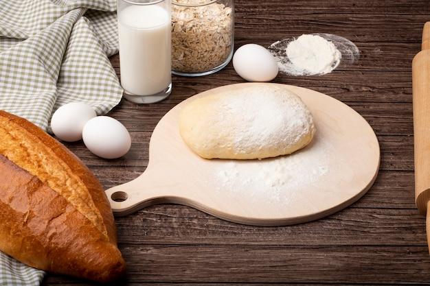 木製の背景にバゲットの卵ミルクオート麦フレークとまな板の上の生地と小麦粉の側面図