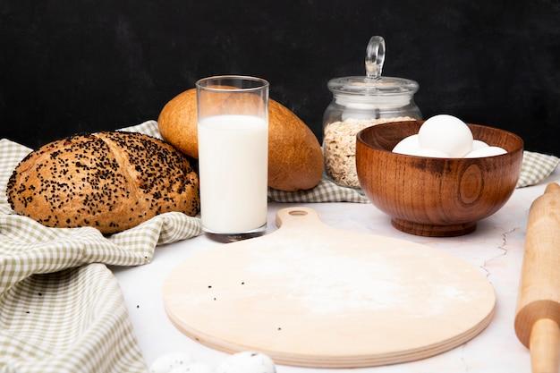 Вид сбоку стакан молока с миску яиц и разделочную доску с початками и овсяные хлопья на белой поверхности и черном фоне с копией пространства