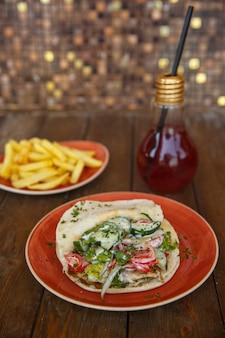 Куриный донер с листьями салата, огурцом, помидорами и зеленью в лаваше