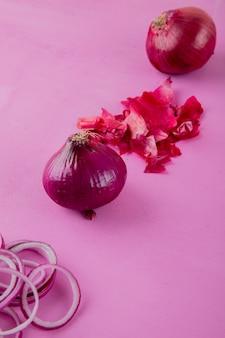 Вид сбоку нарезанный и весь лук с кожей на фиолетовом фоне с копией пространства