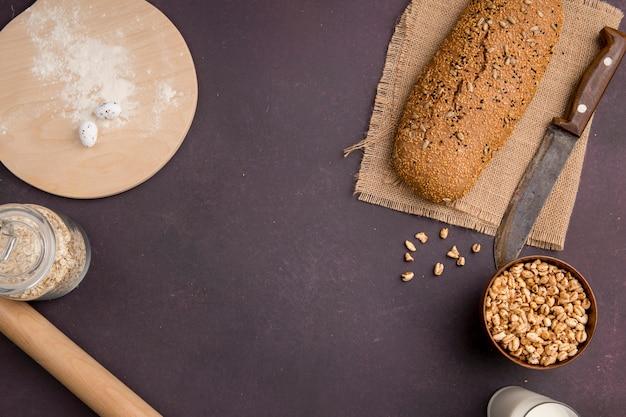 トウモロコシとオート麦フレークと荒布を着たバゲットとナイフの平面図とコピースペースとあずき色の背景にまな板の上の小麦粉