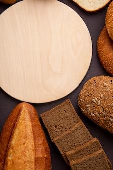 あずき色の背景にまな板とバゲットコブライ麦パンのスライスとしてパンのトップビュー