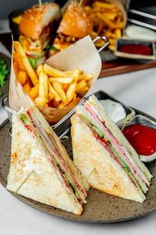 フライドポテトケチャップとマヨネーズを添えたクラブサンドイッチ