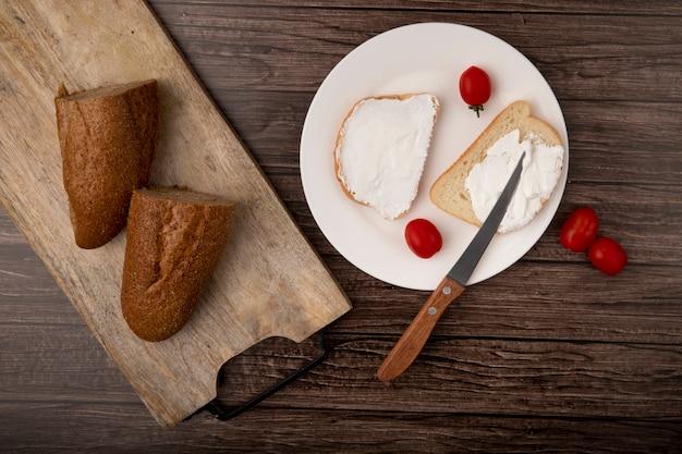 まな板の上半分のバゲットでカットされたパンのトップビューと木製の背景にトマトとナイフでスライスした白パンのプレート