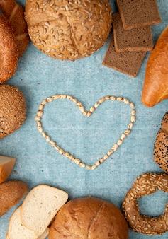 青の背景に周りのパンの種類が異なるハート型のトウモロコシのトップビュー