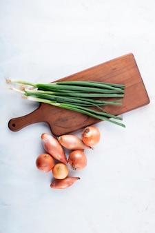 Вид сверху овощей как зеленый лук на разделочной доске и лук-шалот на белом фоне с копией пространства