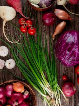 木製の背景にタマネギ大根ニンニクキャベツとして野菜のトップビュー