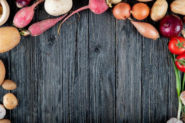 コピースペースを持つ木製の背景に大根タマネギポテトトマトとして野菜のトップビュー