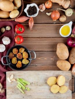 コピースペースを持つ木製の背景にポテトチップスバター黒コショウでトマトポテトニンニクとして野菜のトップビュー