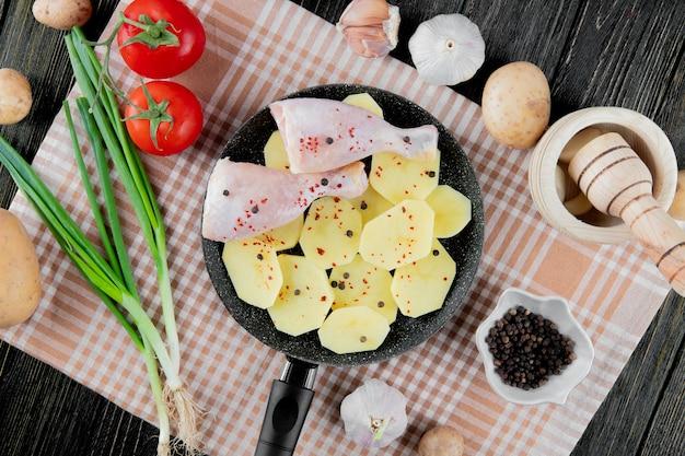 Вид сверху овощей, как томатный лук, чеснок, картофель с кастрюлей картофеля и кусочки куриной ножки и черный перец на деревянном фоне