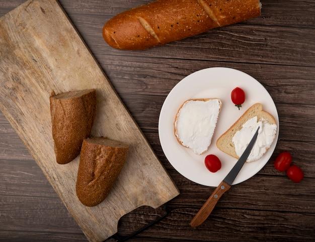 木製の背景のプレートにナイフとトマトの半分のバゲットと白パンのスライスにカットのトップビュー