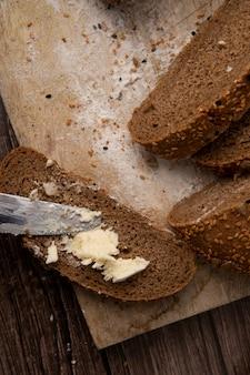木製の表面と背景のパンのスライスにバターを塗るナイフのトップビュー