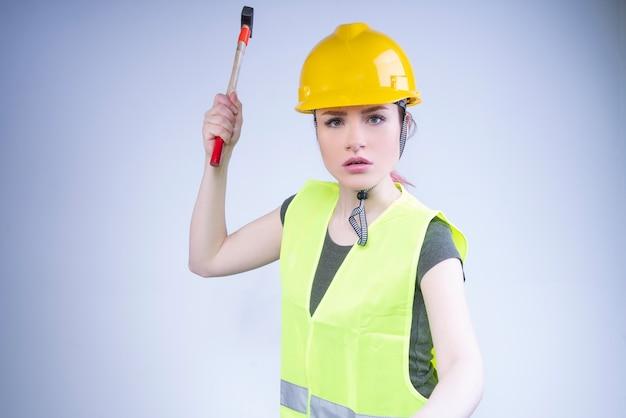 Раздраженный строитель в желтом жилете размахивает молотком