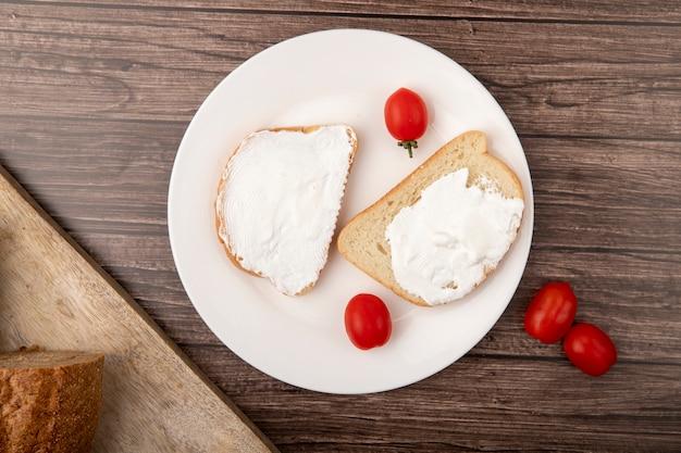 Вид сверху тарелку с ломтиками хлеба, намазанными творогом и помидорами на деревянном фоне