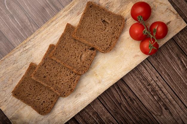 木製の背景にまな板の上のスライスしたライ麦パンとトマトのトップビュー