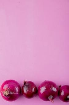 Вид сверху весь красный лук на фиолетовом фоне с копией пространства