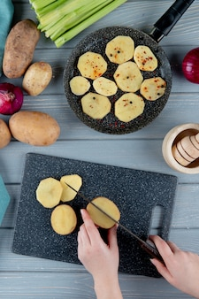 木製の背景にまな板とジャガイモのパンのスライス女性セロリとタマネギの女性手切断ジャガイモの平面図
